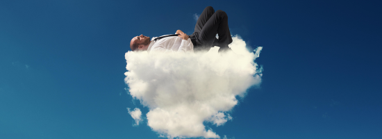 A man in a business suit asleep on a fluffy cloud