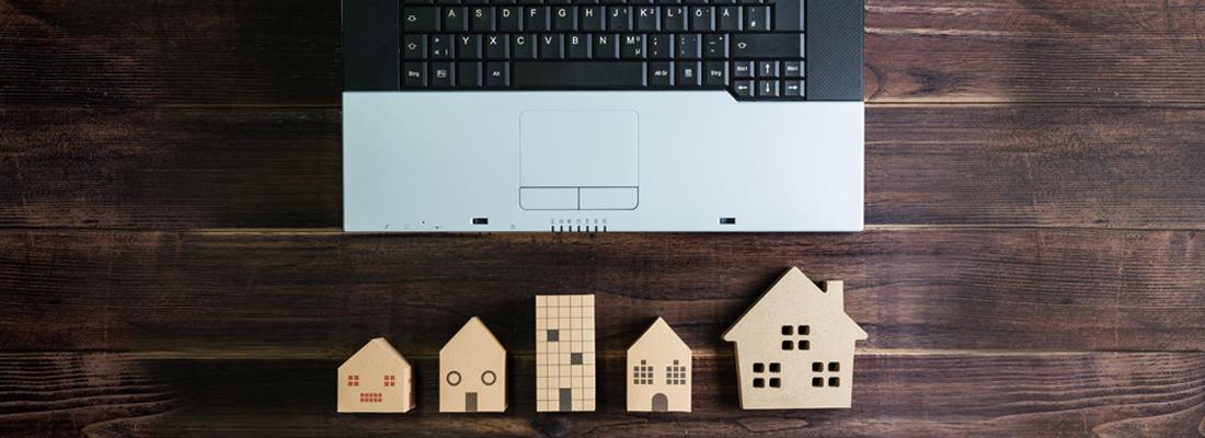 ノートパソコンの側に置かれた木製の住宅模型