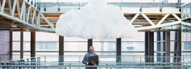 ラップトップを持った男性と頭の上の雲