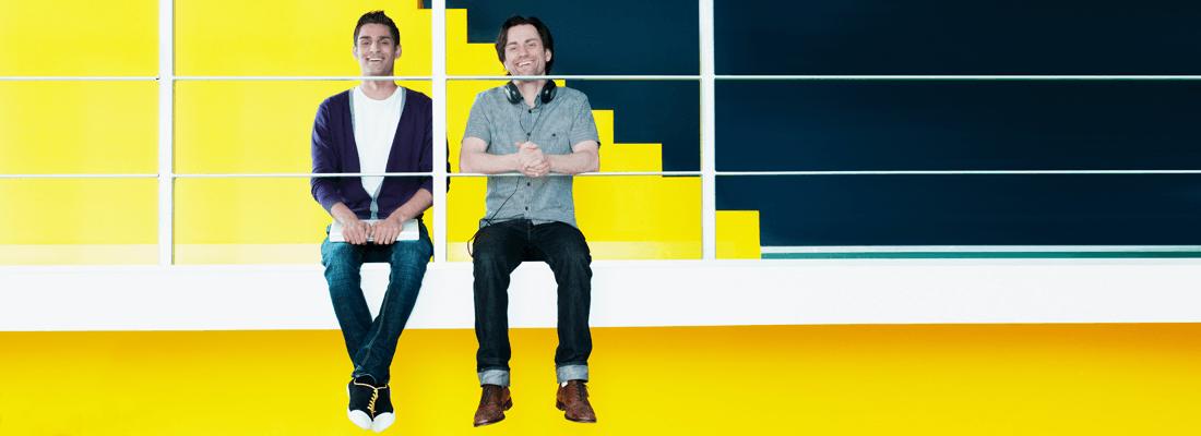 オフィス内で黄色い背景の前にいる2人の幸せそうな男性